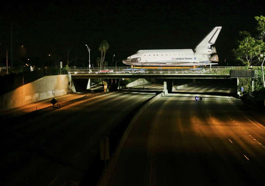 The space shuttle Endeavour makes it's way down Manchester Blvd. over a closed 405 fwy in Inglewood, Calif., Friday, Oct. 12, 2012. Endeavour's 12-mile road trip kicked off shortly before midnight Thursday as it moved from its Los Angeles International Airport hangar en route to the California Science Center, its ultimate destination. (AP Photo/Chris Carlson) Photo: Chris Carlson / AP