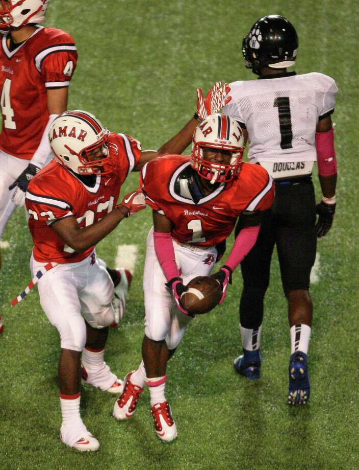Lamar defensive back Cedric Lancaster (1) celebrates his second interception of the night with teammate John Bonney as intended target Westside's Vermaine Newman walks off the field during the second half of a high school football game, Saturday, October 13, 2012 at Delmar Stadium in Houston, TX. Photo: Eric Christian Smith, For The Chronicle