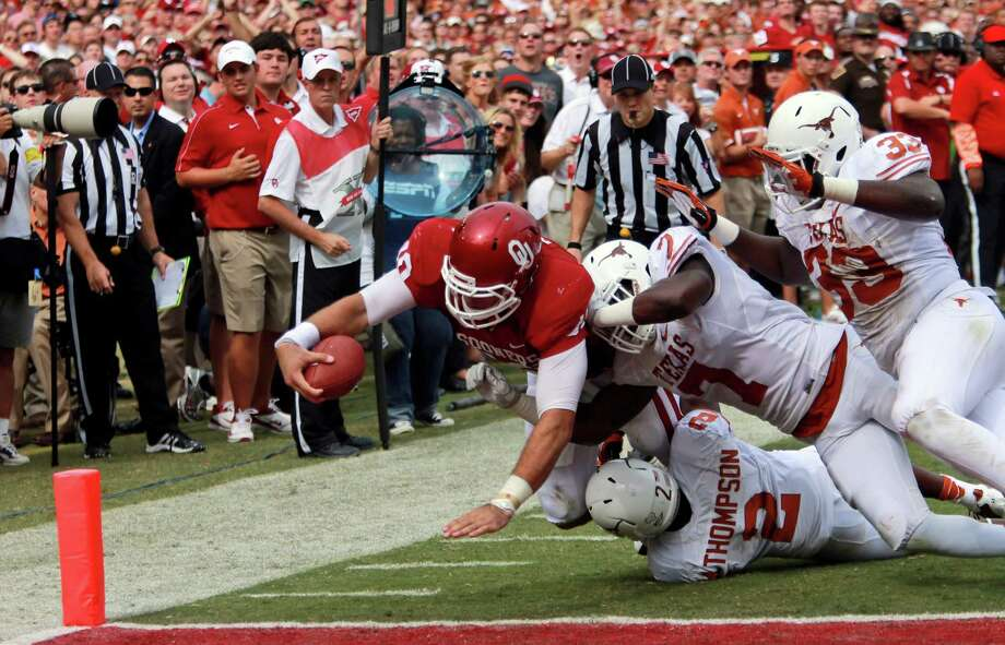Oklahoma quarterback Blake Bell (10) stretches for the gaol line scoring a touchdown against Texas linebacker Steve Edmond (33),  defensive back Mykkele Thompson (2) and linebacker Demarco Cobbs (7) during the first half of an NCAA college football game at the Cotton Bowl Saturday, Oct. 13, 2012, in Dallas. (AP Photo/Michael Mulvey) Photo: Michael Mulvey, Associated Press / FR170767 AP