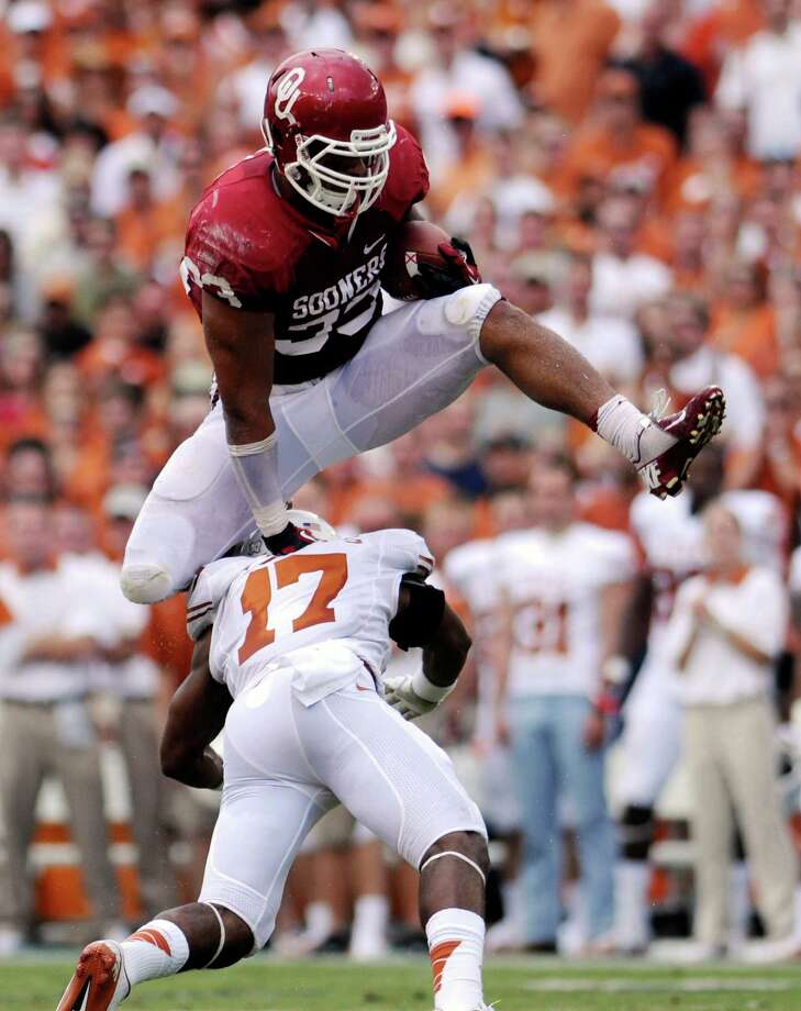 Oklahoma fullback Trey Millard hurdles Texas saferty Adrian Phillips during the first quarter of an NCAA college football game at the Cotton Bowl Saturday, Oct. 13, 2012, in Dallas. (AP Photo/The Daily Texan, Lawrence Peart) Photo: Lawrence Peart, Associated Press / The Daily Texan