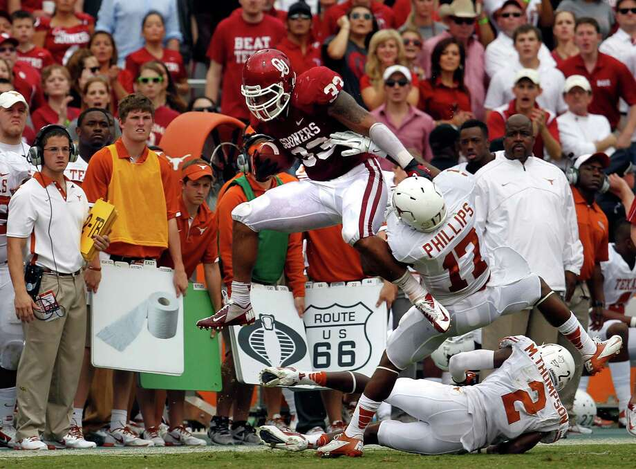 DALLAS, TX - OCTOBER 13:  Trey Millard #33 of the Oklahoma Sooners carries the ball against Adrian Phillips #17 of the Texas Longhorns and Mykkele Thompson #2 of the Texas Longhorns at Cotton Bowl on October 13, 2012 in Dallas, Texas. The Oklahoma Sooners beat the Texas Longhorns 63-21. Photo: Tom Pennington, Getty Images / 2012 Getty Images