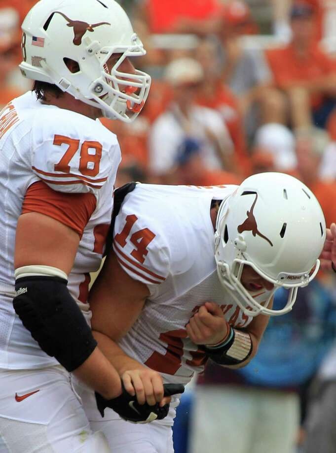 Texas quarterback David Ash (14) is helped by teammate offensive tackle Josh Cochran (78) as he leaves the game injured during the second half of an NCAA college football game against Oklahoma at the Cotton Bowl Saturday, Oct. 13, 2012, in Dallas. Oklahoma  won 63-21. (AP Photo/LM Otero) Photo: LM Otero, Associated Press / AP