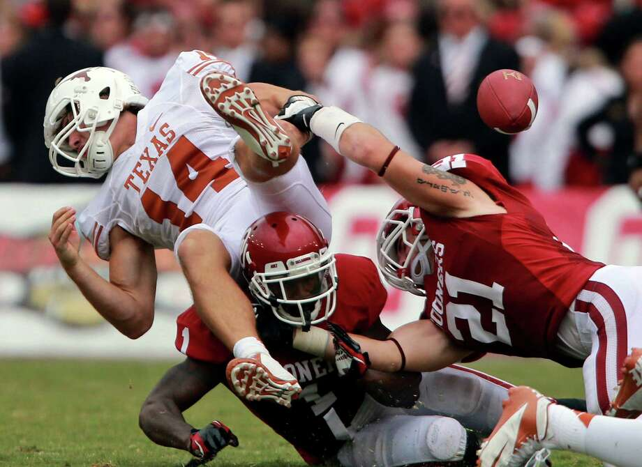 Oklahoma 63, Texas 21Texas quarterback David Ash (14) fumbles after he was sacked by Oklahoma linebacker Tom Wort (21) and defensive back Tony Jefferson (1) during the second half of an NCAA college football game at the Cotton Bowl Saturday, Oct. 13, 2012, in Dallas. Oklahoma  won 63-21. (AP Photo/Michael Mulvey) Photo: Michael Mulvey, Associated Press / AP-170767