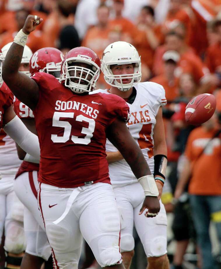 Oklahoma defensive tackle Casey Walker (53) celebrates his sack of Texas quarterback David Ash (14) during the second half of an NCAA college football game at the Cotton Bowl Saturday, Oct. 13, 2012, in Dallas.  Ash left the game injured after the play and did not return. Oklahoma won 63-21. (AP Photo/Michael Mulvey) Photo: Michael Mulvey, Associated Press / AP-170767
