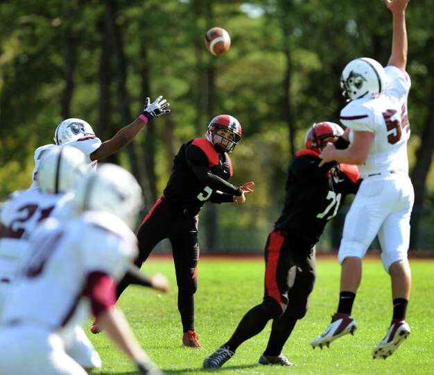 Albany Academy's quarterback Eric Woods (5), center, throws a pass during their football game agains