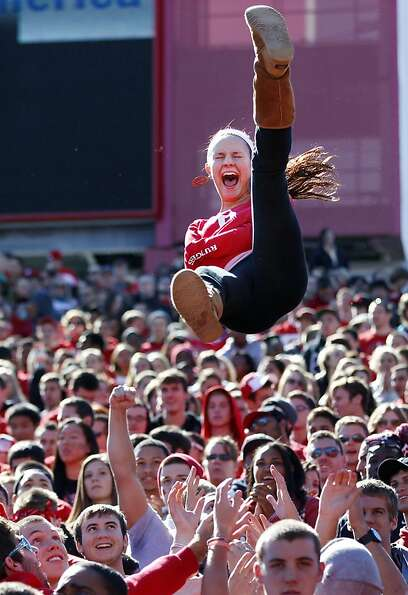 A fan is tossed in the air after a Rutgers touchdown during the first half of an NCAA college footba