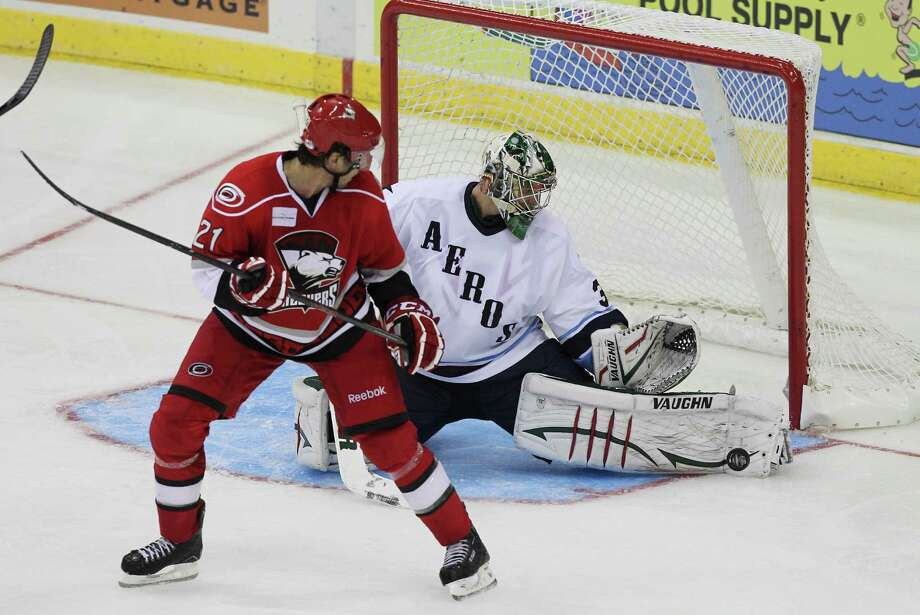 Goalie Matt Hackett #31 of the Houston Aeros makes a pad save on a shot deflected by  Tim Wallace #21 of the Charlotte Checkers in the third period during an AHL hockey game between the the Charlotte Checkers and the Houston Aeros, Saturday, October 13 2012 at the Toyota Center in Houston, Texas. (Bob Levey/For The Chronicle) Photo: Bob Levey, Houston Chronicle / ©2012 Bob Levey