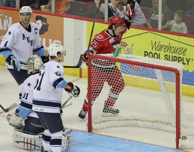 Chris Terry #25 of the Charlotte Checkers slips a rebound shot behind goalie Matt Hackett #31 of the