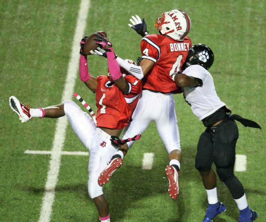 Cedric Lancaster (1) intercepts a pass intended for Westside wide receiver Vermaine Newman and gets an assist from Lamar teammate John Bonney in Saturday's District 20-5A game at Delmar Stadium. Lamar dominated from the get-go in its 42-7 win over the rival Wolves. Photo: Eric Christian Smith