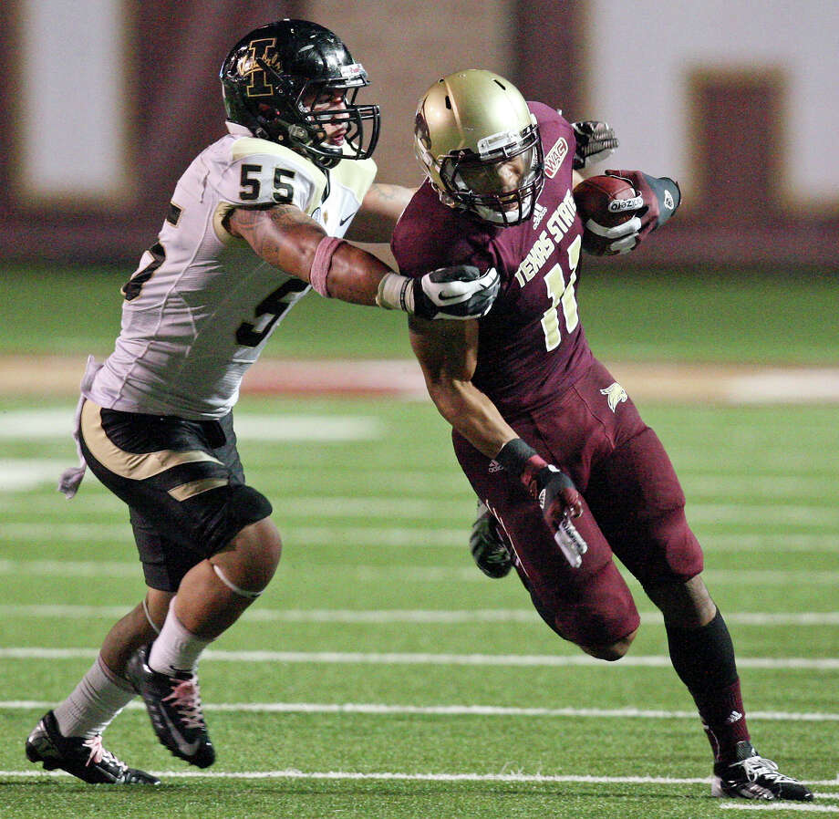 Texas State Bobcats' Tim Hawkins looks for room around Idaho Vandals' Homer Mauga during second half action Saturday Oct. 13, 2012 at Bobcat Stadium in San Marcos, Tx. Texas State won 38-7. Photo: Edward A. Ornelas, Express-News / © 2012 San Antonio Express-News