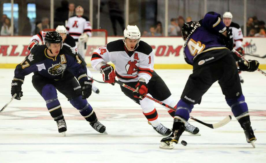 Albany Devil's Adam Henrique (14), center, goes for a loose puck as Manchester Monarch's Thomas Hickey (37), left, and Nick Deslauriers (4), right defend during their hockey game on Saturday, Oct. 13, 2012, at Times Union Center in Albany, N.Y. (Cindy Schultz / Times Union) Photo: Cindy Schultz / 00019578A