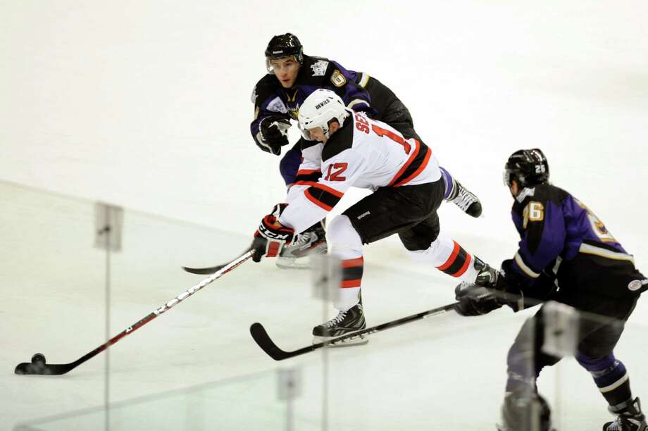 Albany Devils' Tim Sestito (12), center, moves the puck as Manchester Monarchs' David Kolomatis (6), left, and Tyler Toffoli (26) defend during their hockey game on Saturday, Oct. 13, 2012, at Times Union Center in Albany, N.Y. (Cindy Schultz / Times Union) Photo: Cindy Schultz / 00019578A