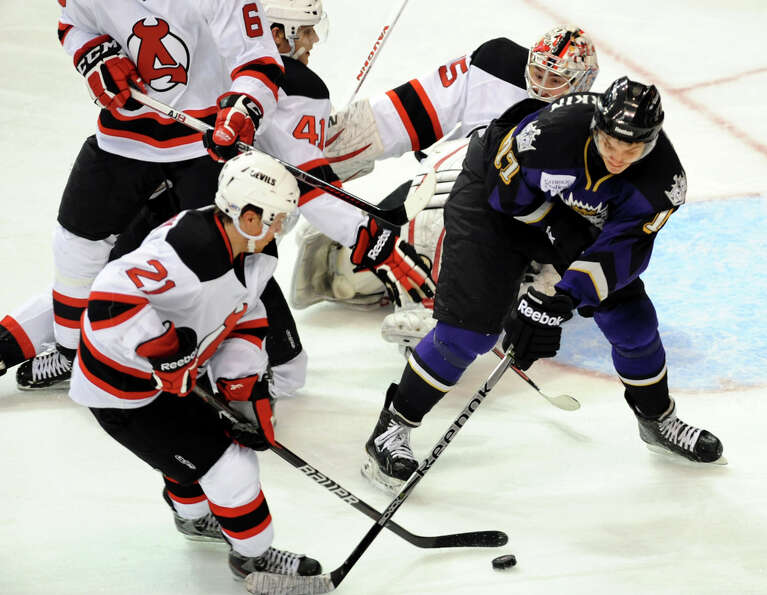 Albany Devils'  (21), left, and Manchester Monarchs' David Kolomatis (17), right, battle for the puc