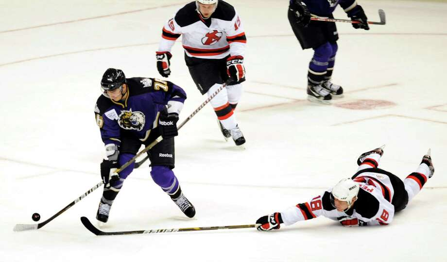 Manchester Monarchs' Slava Voynov (76), left, steers the puck clear of Albany Devils' Harri Pesonen (18), right, during their hockey game on Saturday, Oct. 13, 2012, at Times Union Center in Albany, N.Y. (Cindy Schultz / Times Union) Photo: Cindy Schultz / 00019578A