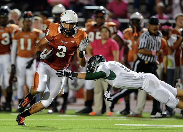 Madison's Dannon Cavil (3) avoids Reagan's Efren Rodriguez (17) during a 26-5A Football game between the Reagan Rattlers and the Madison Mavericks at Heroes Stadium in San Antonio, Saturday, October 13, 2012.