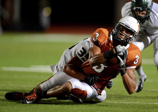 Madison's Dannon Cavil (3) is brought down by Reagan's Paco Dickinson (35) during a 26-5A Football game between the Reagan Rattlers and the Madison Mavericks at Heroes Stadium in San Antonio, Saturday, October 13, 2012.