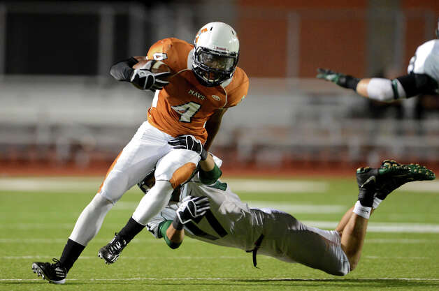 Madison's Byron Daniels (4) is tackled by Reagan's Efren Rodriguez (17) during a 26-5A Football game between the Reagan Rattlers and the Madison Mavericks at Heroes Stadium in San Antonio, Saturday, October 13, 2012.