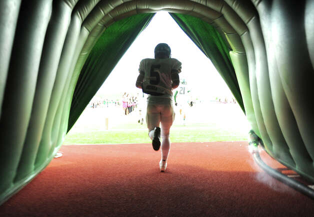 Reagan's C.J. Cavazos (5) runs through a tunnel onto the field before a 26-5A Football game between the Reagan Rattlers and the Madison Mavericks at Heroes Stadium in San Antonio, Saturday, October 13, 2012.