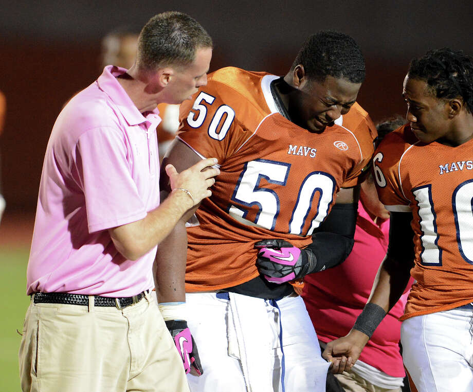 Madison trainer Jason York helps Kevin Brown (50) from the field during a 26-5A Football game between the Reagan Rattlers and the Madison Mavericks at Heroes Stadium in San Antonio, Saturday, October 13, 2012.