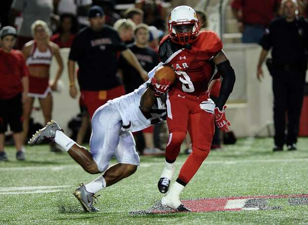 Lamar player Mike Venson is taken down by McMurry defensive player during Lamar University football game against McMurry University at Provost Umphrey Stadium on Saturday, October 13, 2012. Photo taken: Randy Edwards/The Enterprise