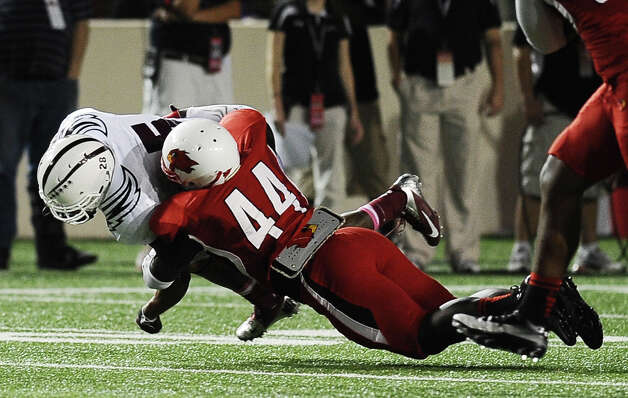McMurry running back Paxton Grayer is tackled by linebacker Ronnie Jones Jr. during Lamar University football game against McMurry University at Provost Umphrey Stadium on Saturday, October 13, 2012. Photo taken: Randy Edwards/The Enterprise