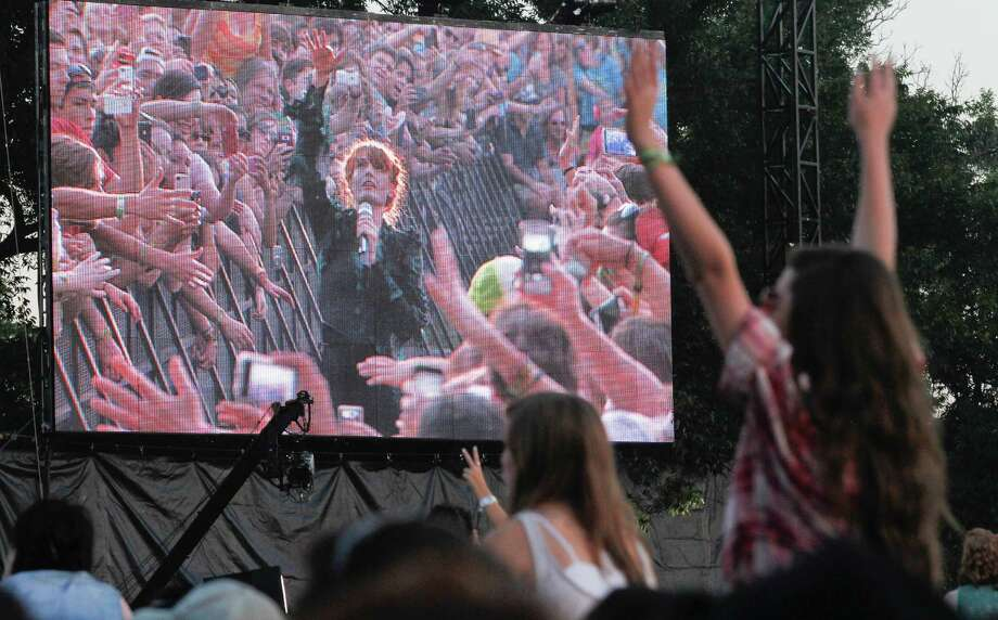 Fans cheer as Florence + the Machine's Florence Mary Leontine Welch, pictured on the video screen, walks through the crowd at the Austin City Limits Music Festival, Friday, Oct. 12, 2012, in Austin, Texas.(Photo by Jack Plunkett/Invision/AP) Photo: Jack Plunkett, Associated Press / Invision