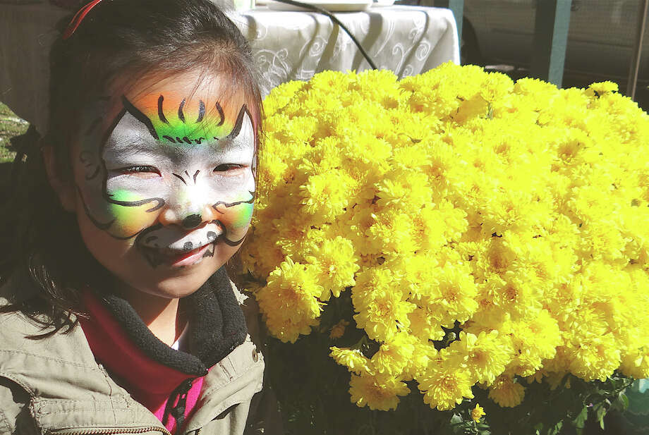 Abby Song, 6, of Fairfield, sports a cool design painted on her face Saturday at Great Beginnings Montessori School's Harvest Fest on Town Hall Green. Photo: Mike Lauterborn / Fairfield Citizen contributed