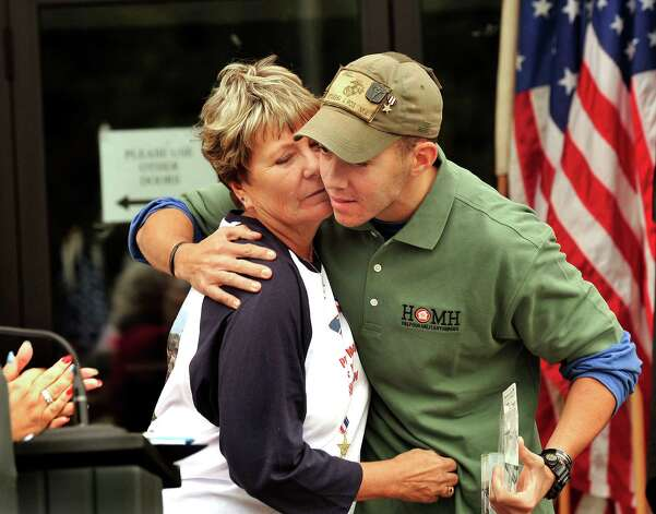 Mary Angell is embraced by her son,Todd Angell, after presenting him with the Warrior Award during the Walk of Honor ceremony at the Danbury War Memorial Sunday, Oct. 14, 2012. Photo: Michael Duffy