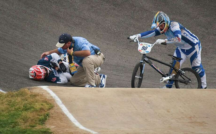 Kyle Bennett (88) of Conroe, Texas, is attended to by a course official as Ramiro Marino of Argentina picks up his bike to finish the race after a crash during the quarterfinals of BMX cycling at the 2008 Summer Olympic Games, Wednesday, Aug. 20, 2008, in Beijing. ( Smiley N. Pool / Chronicle ) Photo: Smiley N. Pool, Houston Chronicle / Houston Chronicle
