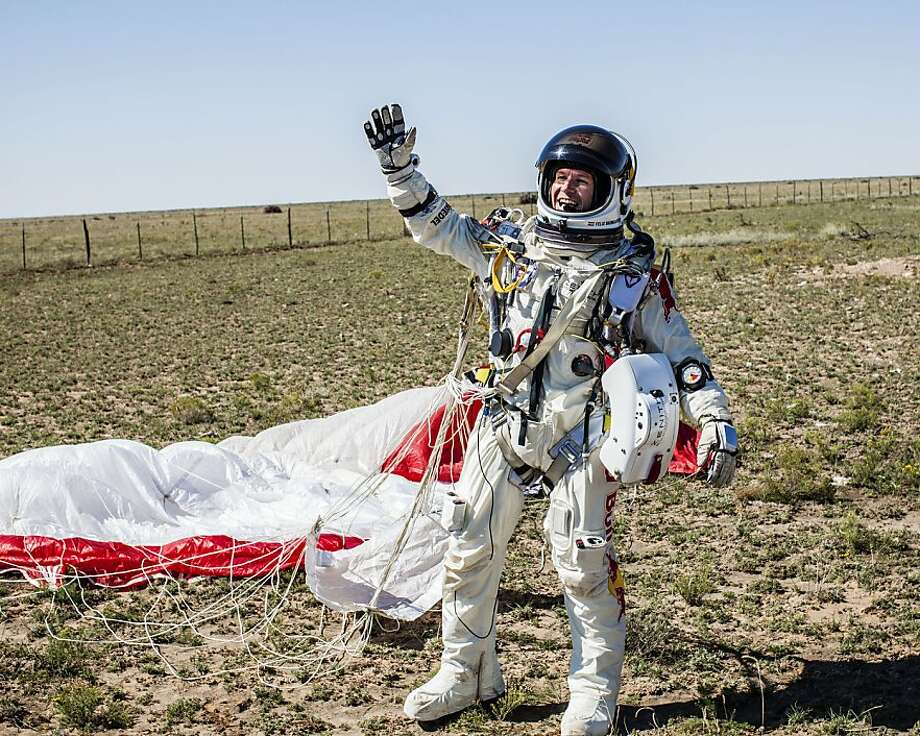Felix Baumgartner of Austria celebrating after successfully completing the final manned flight for Red Bull Stratos in Roswell, New Mexico on October 14, 2012. The Austrian daredevil became the first man to break the sound barrier in a record-shattering freefall jump from the edge of space, organizers said. The 43-year-old leapt from a capsule more than 24 miles (39 kilometers) above the Earth, reaching a speed of 706 miles per hour (1,135 km/h) before opening his red and white parachute and floating down to the New Mexico desert. Photo: Balazs Gardi, AFP/Getty Images