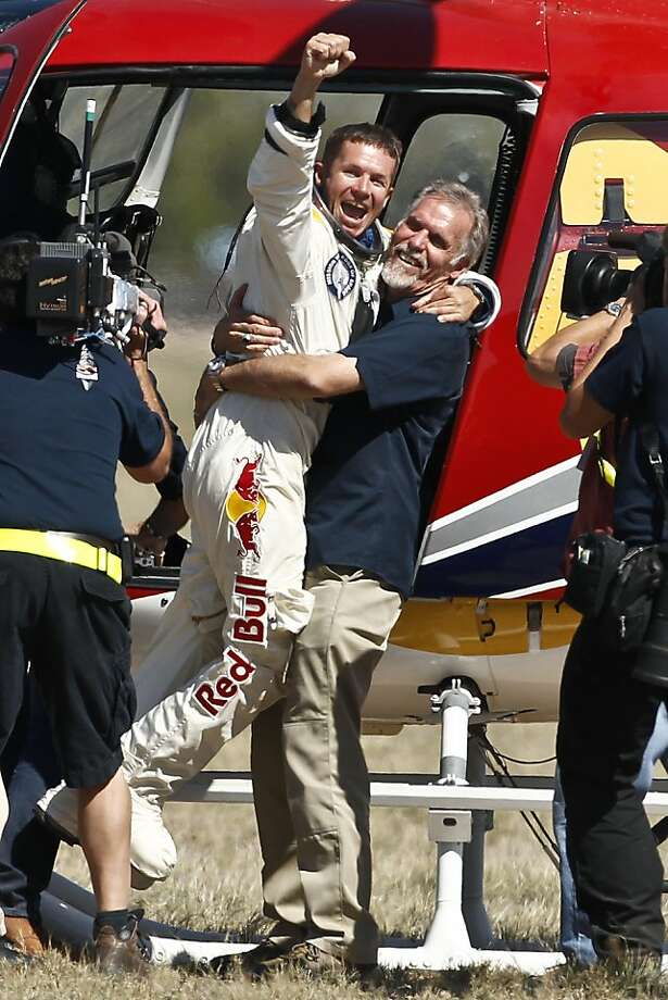 Felix Baumgartner, left, of Austria, celebrates with Art Thompson, Technical Project Director, after successfully jumping from a space capsule lifted by a helium balloon at a height of just over 128,000 feet above the Earth's surface, Sunday, Oct. 14, 2012, in Roswell, N.M.  Baumgartner landed in the eastern New Mexico desert minutes after jumping from his capsule 28,000 feet (8,534 meters), or 24 miles (38.6-kilometer), above Earth. Photo: Ross Franklin, Associated Press