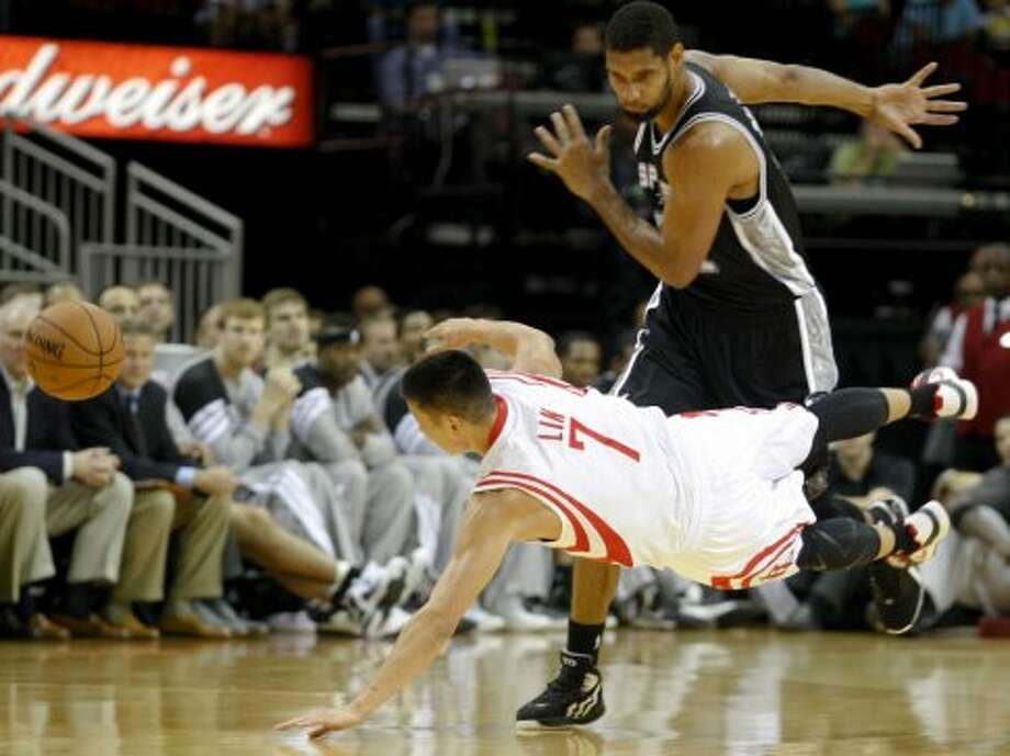 Rockets Jeremy Lin (7) scrambles for  the ball against Spurs Tim Duncan (21) during the first  half of an NBA basketball game, Sunday, Oct. 14, 2012, in Houston. (AP Photo/Eric Kayne) (Associated Press)