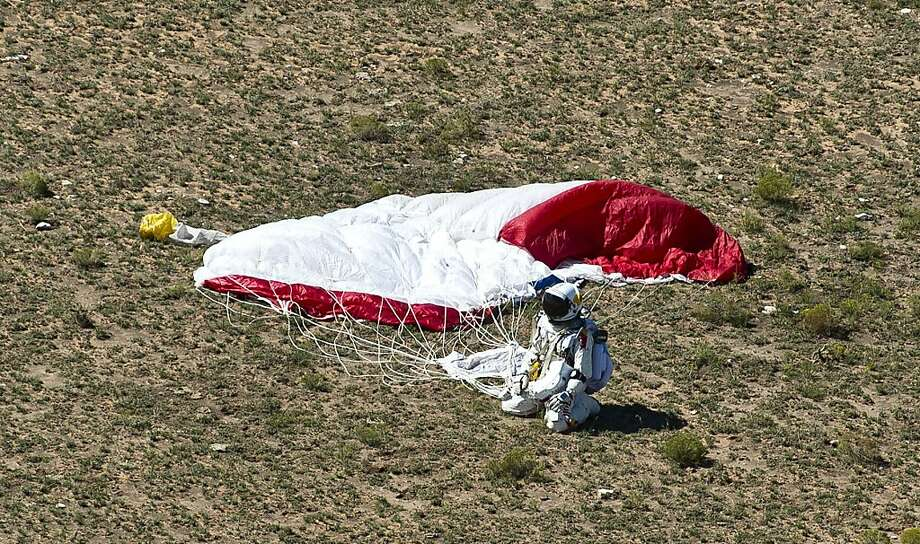 This picture provided by www.redbullcontentpool.com shows pilot Felix Baumgartner of Austria landing in the desert after successfully completing the final manned flight for Red Bull Stratos in Roswell, New Mexico, on October 14, 2012. The Austrian daredevil became the first man to break the sound barrier in a record-shattering freefall jump from the edge of space, organizers said. The 43-year-old leapt from a capsule more than 24 miles (39 kilometers) above the Earth, reaching a speed of 706 miles per hour (1,135 km/h) before opening his red and white parachute and floating down to the New Mexico desert. Photo: Pedrag Vuckovic, AFP/Getty Images