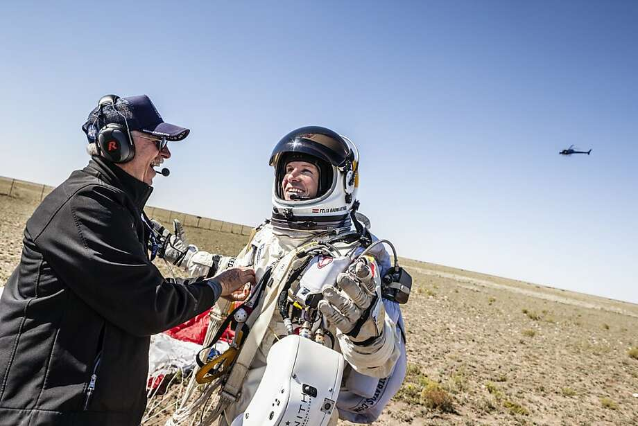 This picture provided by www.redbullcontentpool.com shows life support engineer Mike Todd (L) of the US and pilot Felix Baumgartner of Austria celebrating after successfully completing the final manned flight for Red Bull Stratos in Roswell, New Mexico, on October 14, 2012. The Austrian daredevil became the first man to break the sound barrier in a record-shattering freefall jump from the edge of space, organizers said. The 43-year-old leapt from a capsule more than 24 miles (39 kilometers) above the Earth, reaching a speed of 706 miles per hour (1,135 km/h) before opening his red and white parachute and floating down to the New Mexico desert. Photo: Balazs Gardi, AFP/Getty Images