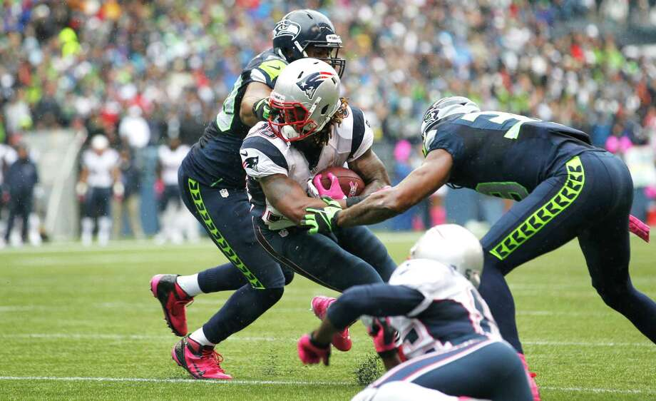 New England Patriots' Brandon Bolden has his facemask grabbed by Seattle Seahawks' K.J. Wright, left, as Seahawks' Brandon Browner moves in for the tackle at right in the first half of an NFL football game, Sunday, Oct. 14, 2012, in Seattle. Photo: AP