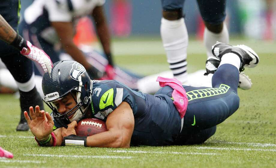 Seattle Seahawks quarterback Russell Wilson goes down after making a run against the New England Patriots in the first half of an NFL football game, Sunday, Oct. 14, 2012, in Seattle. Photo: AP