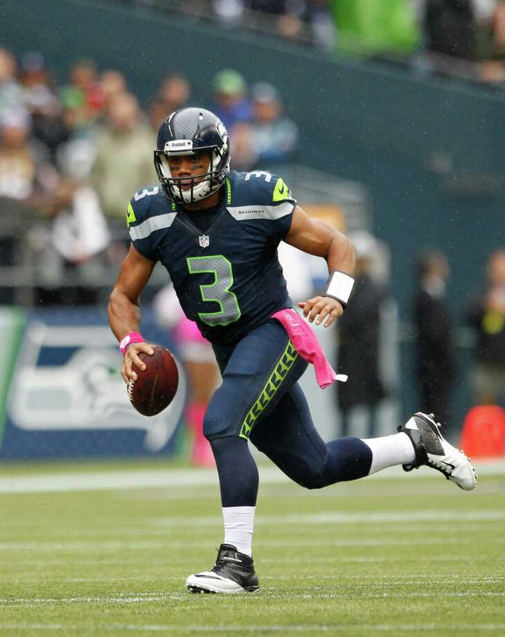 Seattle Seahawks quarterback Russell Wilson scrambles with the ball in the first half of an NFL football game against the New England Patriots, Sunday, Oct. 14, 2012, in Seattle. Photo: AP