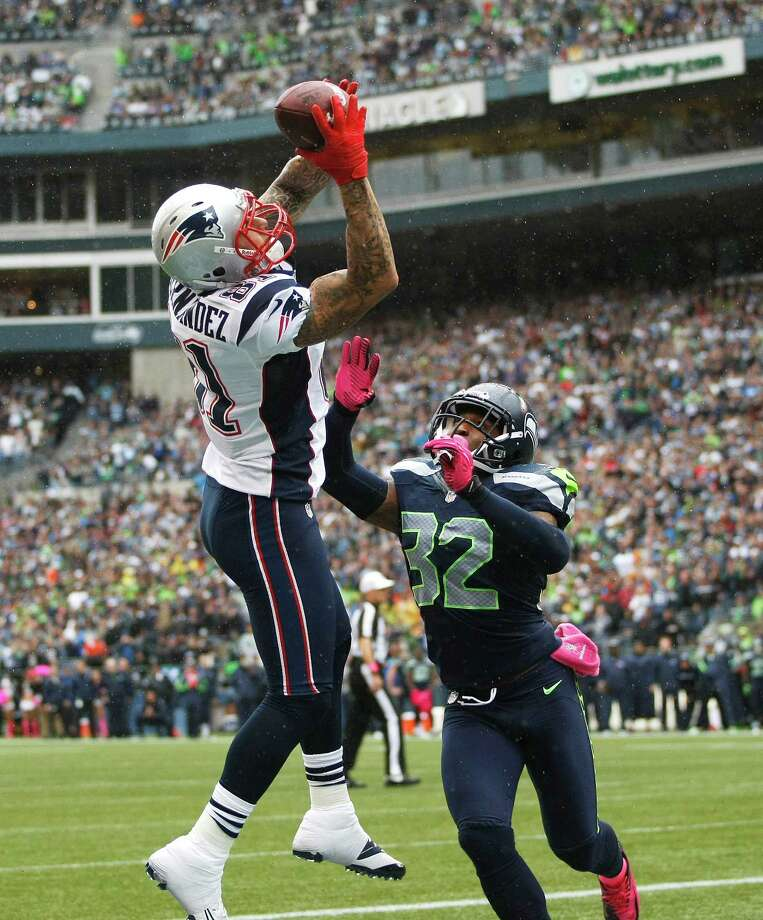 New England Patriots' Aaron Hernandez makes a catch for a touchdown above the defense of Seattle Seahawks' Jeron Johnson (32 )in the first half of an NFL football game, Sunday, Oct. 14, 2012, in Seattle. Photo: AP
