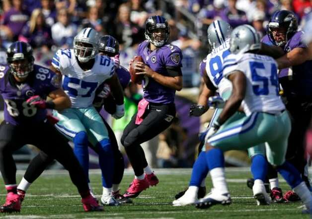 Baltimore Ravens quarterback Joe Flacco, center, looks for a receiver in the first half of an NFL football game against the Dallas Cowboys in Baltimore, Sunday, Oct. 14, 2012. (AP Photo/Patrick Semansky) (Associated Press)