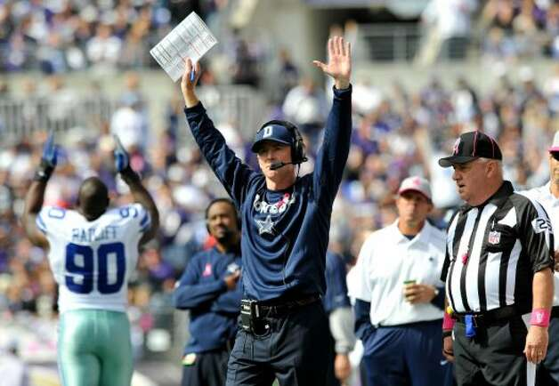 Dallas Cowboys head coach Jason Garrett, center, reacts after officials confirmed running back Felix Jones's touchdown after a review in the first half of an NFL football game against the Baltimore Ravens in Baltimore, Sunday, Oct. 14, 2012. (AP Photo/Gail Burton) (Associated Press)