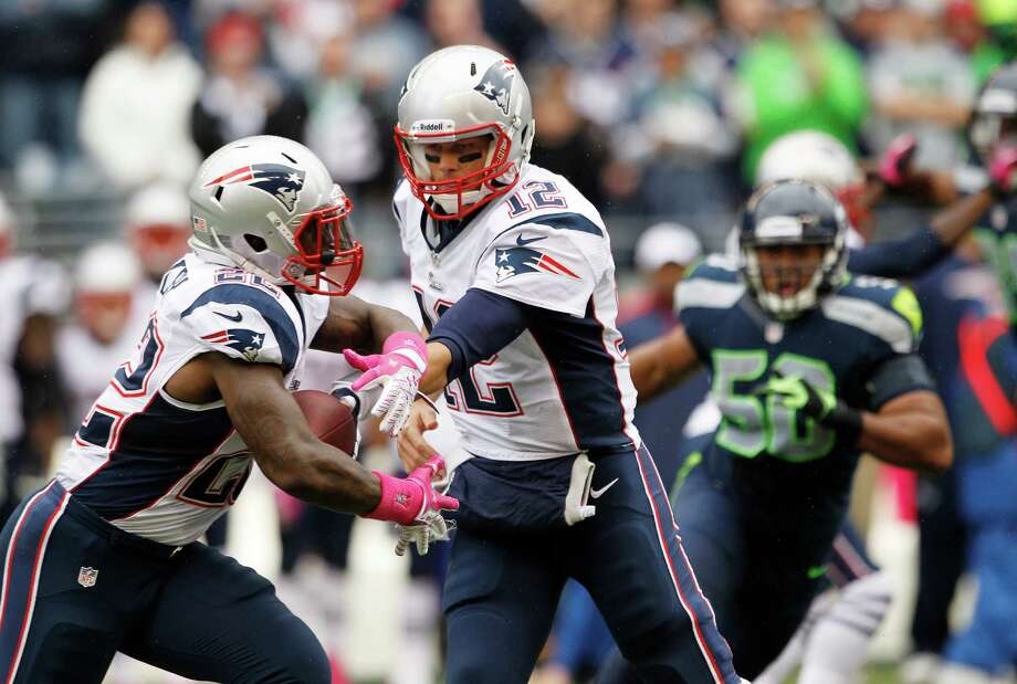 New England Patriots quarterback Tom Brady, right hands off to Patriots' Stevan Ridley, left, in the first half of an NFL football game against the Seattle Seahawks, Sunday, Oct. 14, 2012, in Seattle. Photo: AP