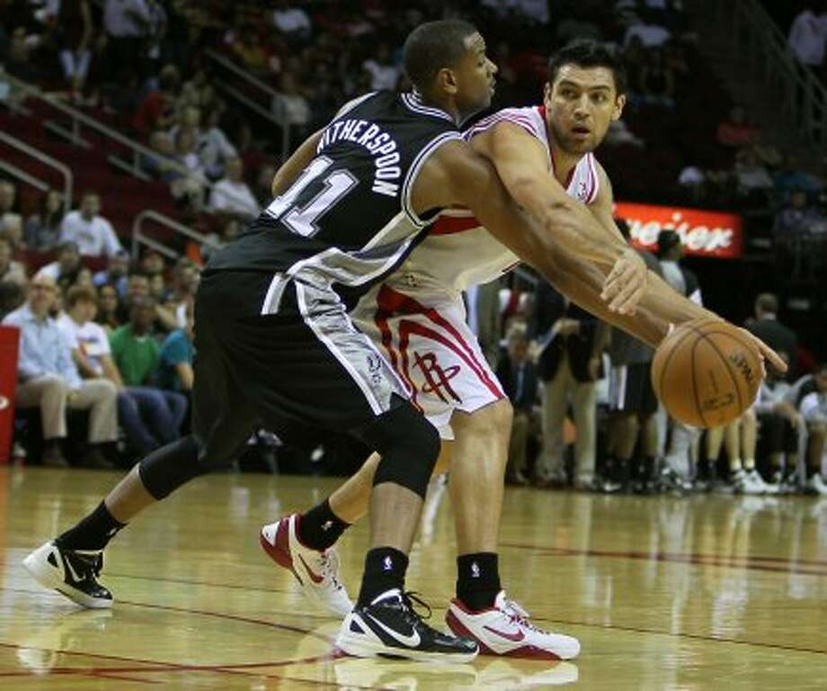 Rockets forward Carlos Delfino is hassled by Wesley Witherspoon of the Spurs. (James Nielsen / © Houston Chronicle 2012)