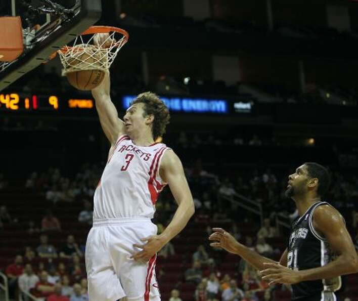 Rockets center Omer Asik dunks the ball as Spurs center Tim Duncah looks on during the first quarter