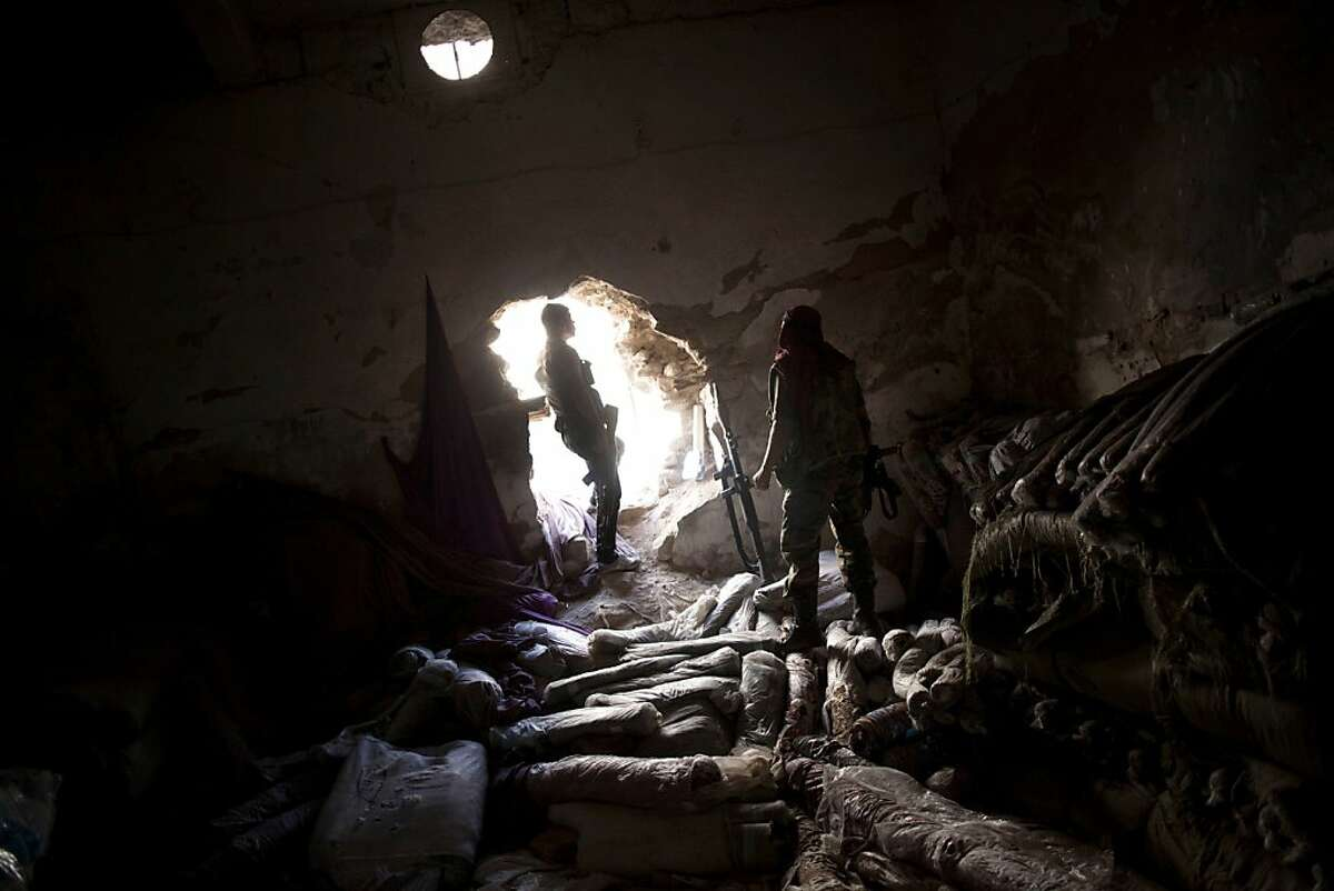 Free Syrian Army fighters are seen in a storage room in the Karmal Jabl district of Aleppo Syria, Sunday, Oct. 14, 2012. Rolls of fabric are seen on the ground. (AP Photo/ Manu Brabo)