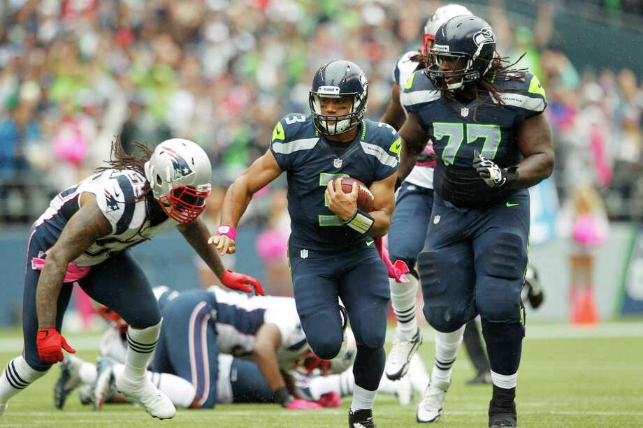Seattle Seahawks quarterback Russell Wilson (3) carries the ball as teammate James Carpenter (77) blocks and New England Patriots linebacker Brandon Spikes, left, moves in for the tackle in the first half of an NFL football game, Sunday, Oct. 14, 2012, in Seattle. Photo: AP