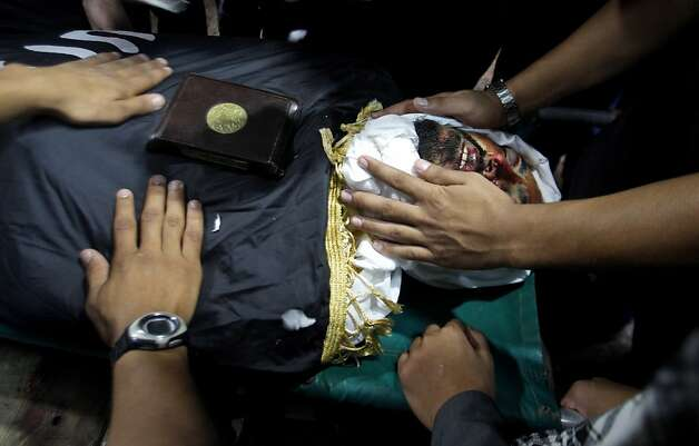 Palestinian mourners gather around the body of Salafi militant Hisham Saidani during his funeral in Bureij refugee camp, central Gaza Strip, Sunday, Oct. 14, 2012. Saidani, a member of a faction of the ultraconservative Salafi trend believed to have ties to al-Qaida, was one of two people killed in an Israeli airstrike on Saturday. Saidani is suspected of carrying out attacks against Israeli and Egyptian targets. (AP Photo/ Hatem Moussa) Photo: Hatem Moussa, Associated Press