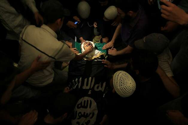 TOPSHOTS Palestinians pay their final respect to the Salafist leader Hisham al-Saedini during his funeral procession at Al-Bureij refugee camp in the central Gaza Strip, on October 14, 2012. Saedini, a top Salafist leader whose Islamist faction has recently fired rockets at Israel was among three people killed in Israeli air strikes on Gaza, sources on both sides said. AFP PHOTO/MAHMUD HAMSMAHMUD HAMS/AFP/GettyImages Photo: Mahmud Hams, AFP/Getty Images