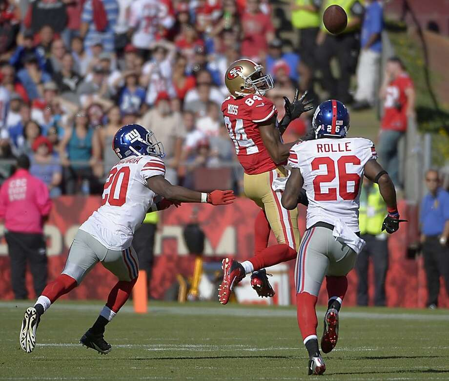 San Francisco 49ers wide receiver Randy Moss (84) catches a pass over New York Giants cornerback Prince Amukamara (20) and free safety Antrel Rolle (26) during the third quarter of an NFL football game in San Francisco, Sunday, Oct. 14, 2012. (AP Photo/Mark J. Terrill) Photo: Mark J. Terrill, Associated Press