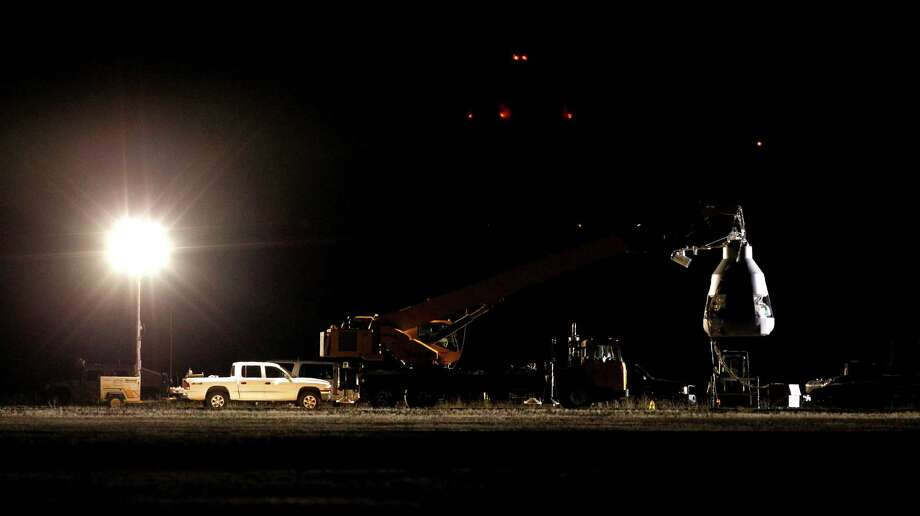 A spotlight illuminates the capsule, ahead of an attempt by Felix Baumgartner to break the speed of sound with his own body by jumping from a space capsule lifted by a helium balloon, Sunday, Oct. 14, 2012, in Roswell, N.M.  Baumgartner plans to jump from an altitude of 120,000 feet, an altitude chosen to enable him to achieve Mach 1 in free fall, which would deliver scientific data to the aerospace community about human survival from high altitudes.(AP Photo/Ross D. Franklin) Photo: Ross Franklin
