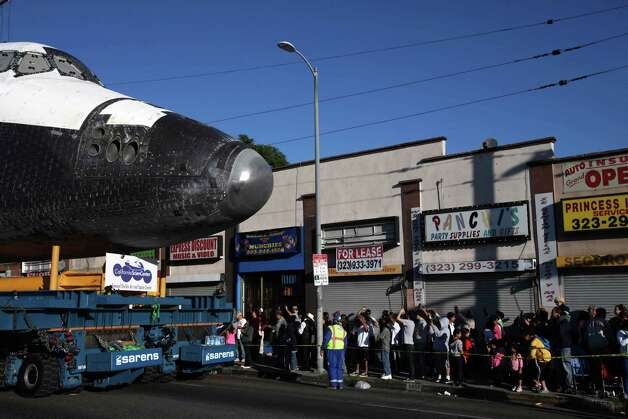 The space shuttle Endeavour slowly moves down Martin Luther King Boulevard on Sunday, Oct. 14, 2012 in Los Angeles.  In thousands of Earth orbits, the space shuttle Endeavour traveled 123 million miles. But the last few miles of its final journey are proving hard to get through. Endeavour's 12-mile crawl across Los Angeles to the California Science Museum hit repeated delays Saturday, leaving expectant crowds along city streets and at the destination slowly dwindling. Officials estimated the shuttle, originally expected to finish the trip early Saturday evening, would not arrive until later Sunday. Photo: AP